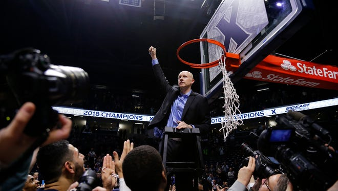 Xavier Musketeers head coach Chris Mack raises a first before cutting down the net after the NCAA Big East game between the Xavier Musketeers and the Providence Friars at the Cintas Center in Cincinnati on Wednesday, Feb. 28, 2018. The Musketeer won its first-ever Big East regular season title with an 84-74 win over Providence.