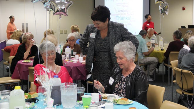 Treasure Health President and CEO Susan de Cuba, standing, speaks to volunteers enjoying lunch.