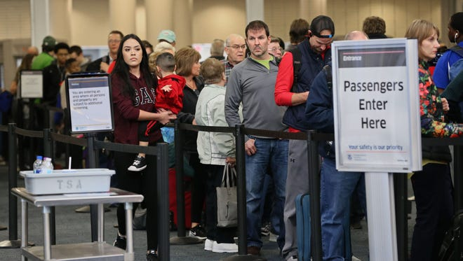 People wait in line to go through security at Mitchell International Airport in Milwaukee.