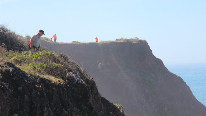 Deputy Bill Holcomb looks down the cliff near the crash site near Mendocino, Calif., as search and rescue volunteers scour the area behind him on Thursday, March 29, 2018, and resume looking for three children, still missing after their parent's SUV plunged into the ocean Monday. Investigators have yet to determine the cause of the crash.