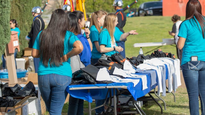 Volunteers at the National Crime Victims' Expo at Young Park hand out free shirts and bags Saturday, April 7, 2018.
