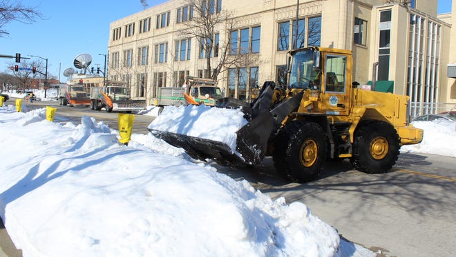 A Green Bay public works crew clears snow Thursday to allow meltwater to flow to storm sewers on Madison Avenue in downtown Green Bay. Temperatures that are expected to reach the 60s this weekend will quickly melt the more than 2 feet of snow that fell on the city during last weekend's storm.