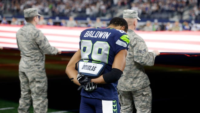 Seahawks wide receiver Doug Baldwin (89) bows his head during the playing of the National Anthem before a Christmas Eve game in Dallas.