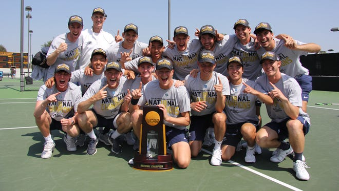 The Middlebury College men's tennis team poses with the NCAA Division III championship trophy.
