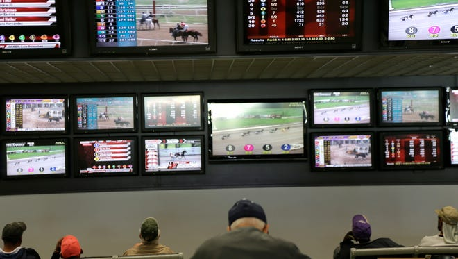 In this Monday, May 14, 2018, file photo, men watch horse racing on an array of screens at Monmouth Park Racetrack in Oceanport, N.J. Now that the U.S. Supreme Court has cleared the way for states to legalize sports betting, the race is on to see who will referee the multi-billion-dollar business expected to emerge from the decision.