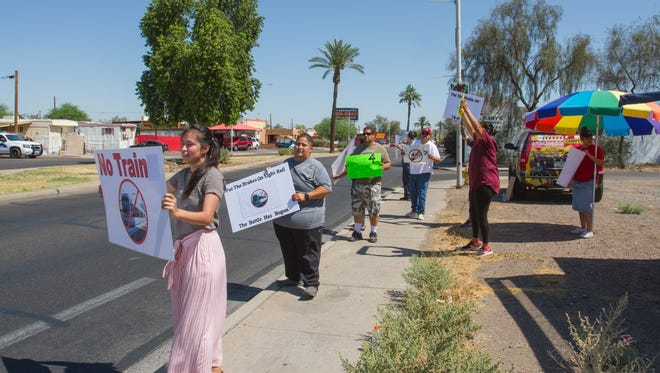 A dozen protesters rallied on Central Avenue in south Phoenix to demonstrate their opposition to the proposed six-mile light-rail extension