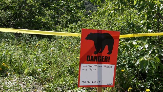 A bear sign and police tape mark a site near a bear attack near Eagle River, Alaska, Wednesday, June 20, 2018.
