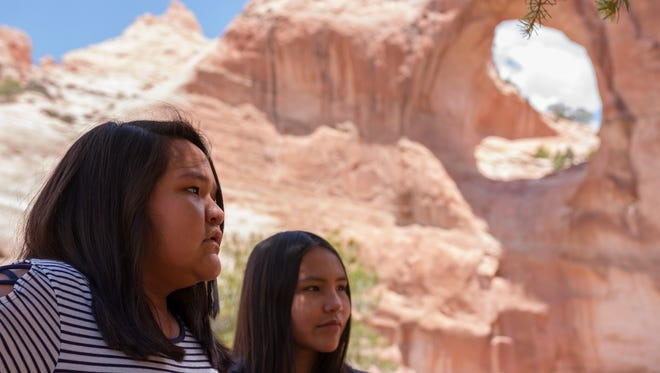 Hailey and Kelly Haven talk to their mother in the shade in front of Window Rock, a giant rock formation that often draws travelers and passerbys to the Navajo Nation.