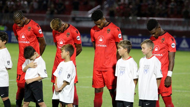 Phoenix Rising players participate in a moment of silence for the late John McCain before its game against the Colorado Springs Switchbacks FC on Saturday night at Phoenix Rising Soccer Complex on Aug. 25, 2018.