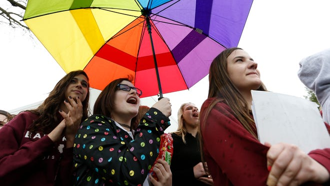 """Dowling Catholic freshman Saffron Edwards, 15 (center), holds up her rainbow-colored umbrella April 8, 2015, during a walkout protesting the private Catholic school's decision not to hire a gay teacher in Des Moines. The school on Friday approved request by students to form a gay-straight alliance at the school, called """"One Human Family."""""""
