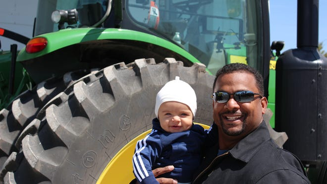 Alfonso Ribeiro and his son, AJ, in front of a tractor on his wife's family farm in southeast Iowa.