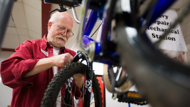 Richard Marmor installs a new brake cable on a bike while volunteering at Recycle Your Bicycle for a Kid in Foster Care in Phoenix on Oct. 25, 2014.