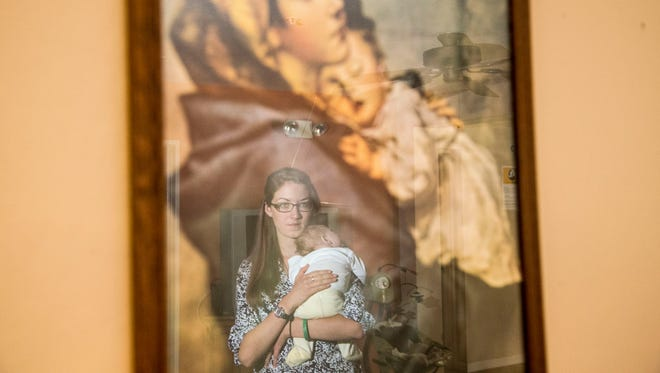 Melissa Peters, a volunteer on staff at Maggie's Place holds one of the resident's baby while her mother makes breakfast on Oct. 25, 2014.