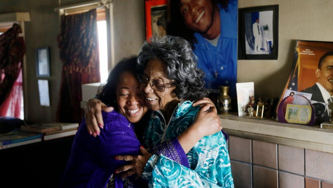 In this Dec. 23, 2014 photo, Lorrain Taylor, left, hugs Arlene Johnson, grandmother of Diamond Jackson, who was shot and killed in his neighborhood in 2009, in Oakland, Calif. Taylor was paying a visit to Jackson's family as part of her duties for the nonprofit 1000 Mothers Against Violence.
