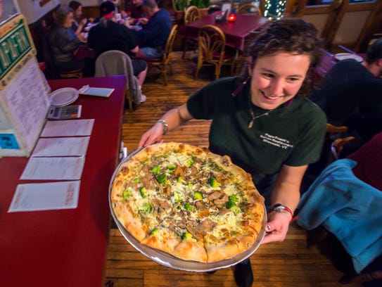 A large pizza heads out to a table of diners at Papa