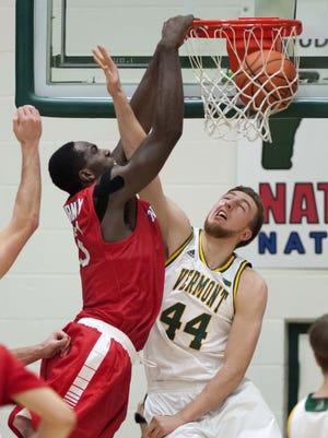 Stony Brook's Jameel Warney jams the ball over the University of Vermont's Nate Rohrer in Burlington on Saturday, January 30, 2016.