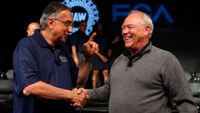 In this July 14, 2015, file photo, Fiat Chrysler Automobiles CEO Sergio Marchionne, left, and UAW President Dennis Williams shake hands during a ceremony to mark the opening of contract negotiations in Detroit. The UAW confirmed Thursday, Oct. 22, 2015, that member ratified a new four-year agreement.