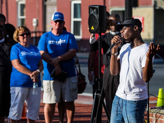 Fifteen year-old Samuel Patterson performs a song he wrote for a vigil at the Middletown town square on Thursday evening. About 100 people gathered in the town's Cochran Square for a prayer vigil and unity march.