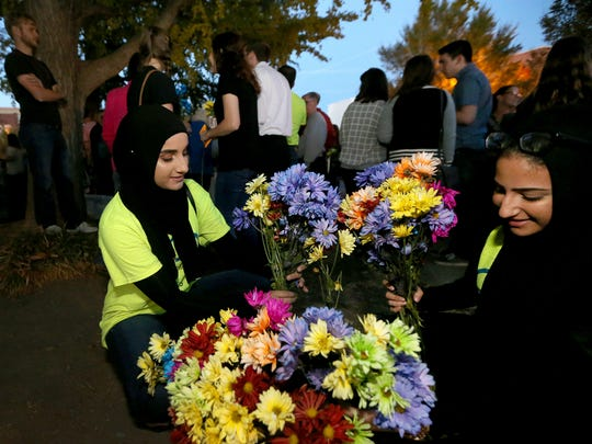 Sarah Alzabet, 16, left, and Haneen Ahmad, 18, divide flowers to pass out during the Murfreesboro Muslim Youth gathering to promote peace and unity Friday, Nov. 18, 2016, on the Square in Murfreesboro.