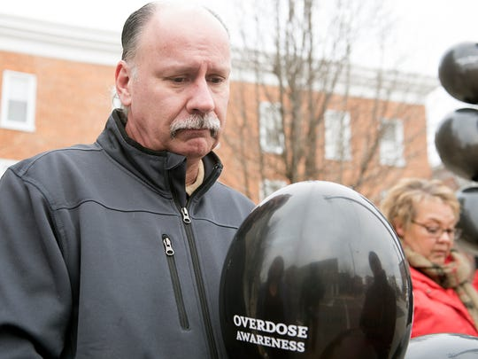 Mike Straley holds a black balloon, which he planned to hang at his Greencastle home in honor of his daughter Leah, who died of a drug overdose on Feb. 14. He received the balloon from Vicki Rhodes, right, who was hanging balloons around the Greencastle square on Tuesday in honor of her daughter Teri, who died in 2015.