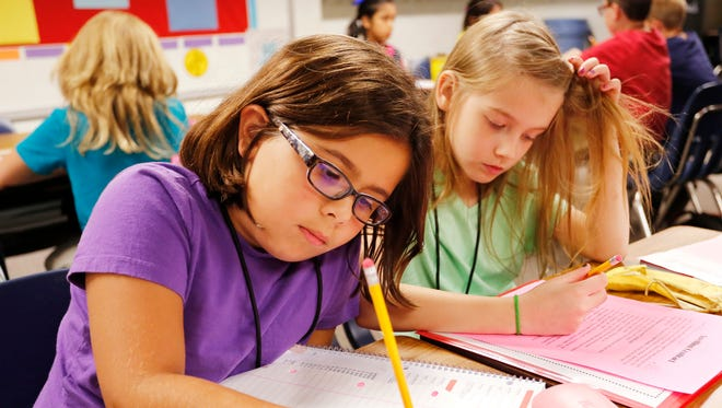 Third graders Sydney North, left, and Kylie Stewart complete homework during the after-school program Tuesday, August 8, 2017, at Murdock Elementary School.