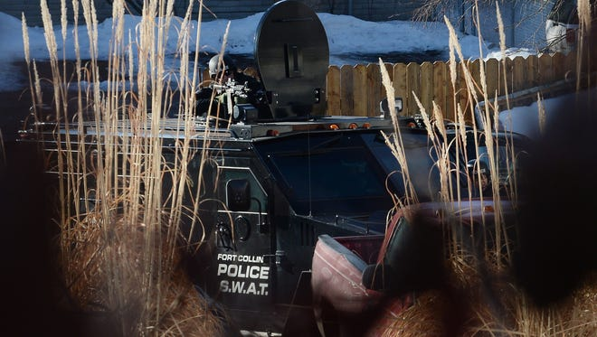 The Fort Collins Police SWAT team waits for a homicide suspect to exit an apartment near the intersection of Prospect Road and Riverside Avenue on Wednesday, Feb. 10, 2016.