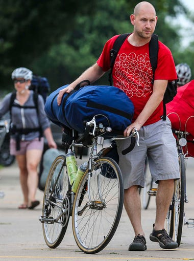 Tony Sergen, left, and Liz Kenyon of Chicago(1st and 2nd RAGBRAI's) gather their belongings and look for a campsite during RAGBRAI 2014 in Rock Valley, Iowa, Saturday July 19, 2014.