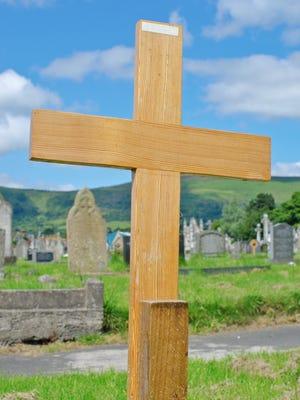 A wooden cross on a pauper's grave.