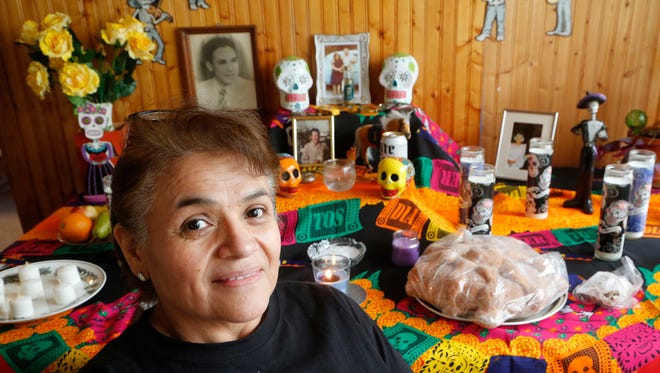 Martha Chavez with the Dia de los Muertos (Day of the Dead) altar of Wednesday, October 26, 2016, in her Monticello home. The altar contains variety of items, such as photographs of deceased relatives and some of their belongings, candles, fruits and other foods.