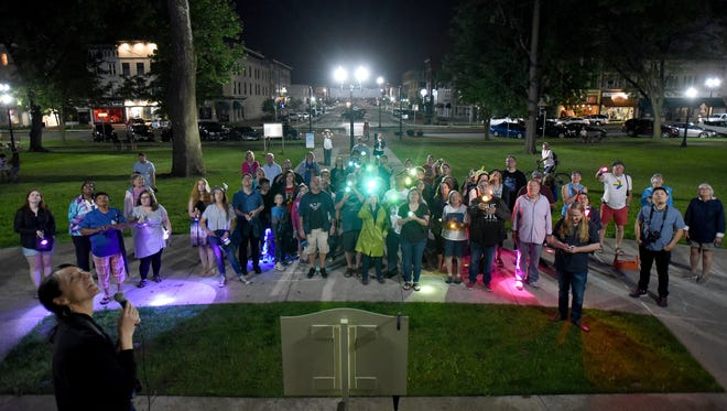Members of the LGBTQ community and allies use gelled flashlights to light the Licking County Courthouse during the People's Pride Light event on Friday, June 8, 2018. After the Licking County Commissioners rejected a request to light the courthouse in rainbow colors for the first Newark Pride celebration community members used gelled flashlights to light the Western facade the courthouse. Newark's first Pride event will be held Saturday, June 9 in downtown Newark.