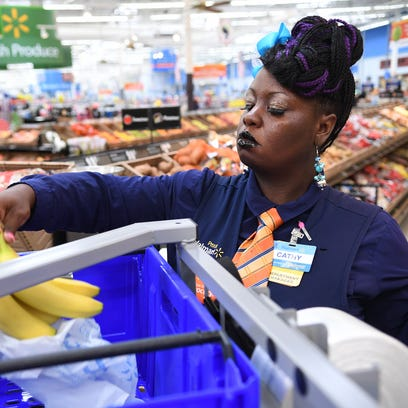 Cathy Booker, Walmart department manager, picks produce for an online order Friday. Walmart has launched an online grocery pick up at four Greenville-area store.