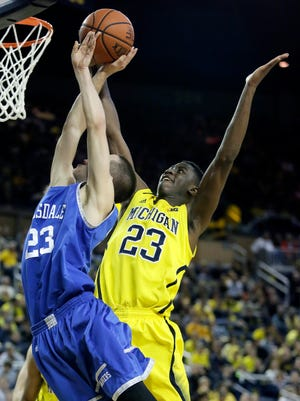 Caris LeVert  of the Michigan Wolverines blocks a shot attempt by Stedman Lowry  of the Hillsdale College Chargers.
