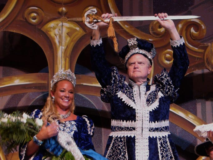 Having just been crowned Don Tristan DeLuna the 65th Collier Merrill holds a sword up high, a symbol of his reign, as he greets his subjects alongside his queen, Clotilde DeMaria, during the DeLuna coronation ball Friday night at the Pensacola Bay Center.