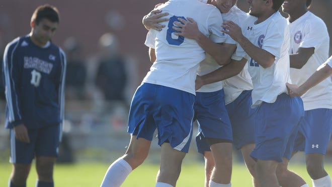 Washington Township's Marc Murgo, left, 8, Scott Graham, center, 16, and Jason Arakelian, right, 12,  celebrate a goal against Eastern in the first half of Friday's sectional final. The Minutemen won 2-0.