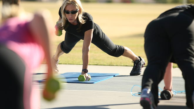 Alison Busher leads weight lifts from the push-up position during cardio exercises in her Desert Boot Camp program at La Quinta Park on Wednesday, February 22, 2012.