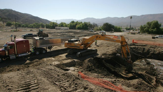 An excavator digs out soil contaminated with lead and polycyclic aromatic hydrocarbons on Aug. 27, 2014, in Fillmore. The soil portion of this Superfund site, where a Texaco oil refinery once stood, has now been removed from the Superfund list, putting the property one step closer to becoming a solar field.