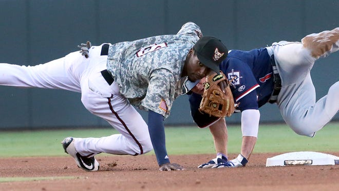 Second baseman Jemile Weeks, left, of the El Paso Chihuahuas falls over base runner Evan Marzilli of the Reno Aces after Weeks fired to first base Monday night at Southwest University Park.