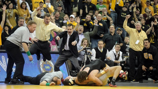 Iowa coaches Tom Brands, left, and Terry Brands, second from left, leap in the air as Mike Evans throws down Ohio State?s Nick Heflin for a 9-4 win in overtime Friday at Carver-Hawkeye Arena.