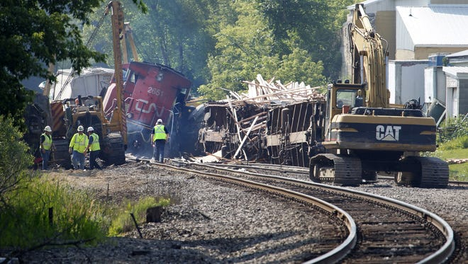 Workers clean up after a train derailment in Slinger on Monday. A southbound Canadian National train struck several Wisconsin & Southern Railroad cars around 8:30 p.m. Sunday at a rail crossing in Slinger, Wis., according to Patrick Waldron, a Canadian National spokesman. The derailment injured at least two people and spilled thousands of gallons of fuel that prompted the evacuation of dozens of homes, but evacuees were allowed to return around 1:30 a.m. Monday, Slinger Fire Chief Rick Hanke said.