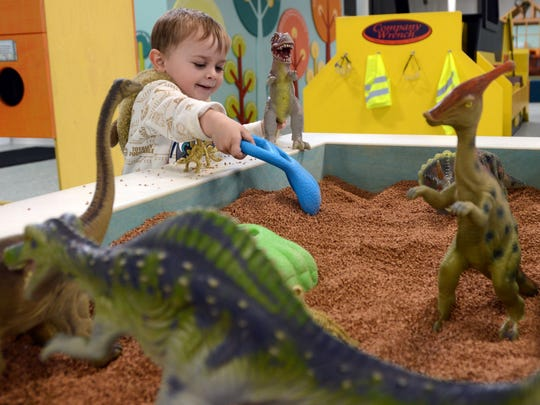 Noah Anderson, 3, from Amanda, plays in the dinosaur