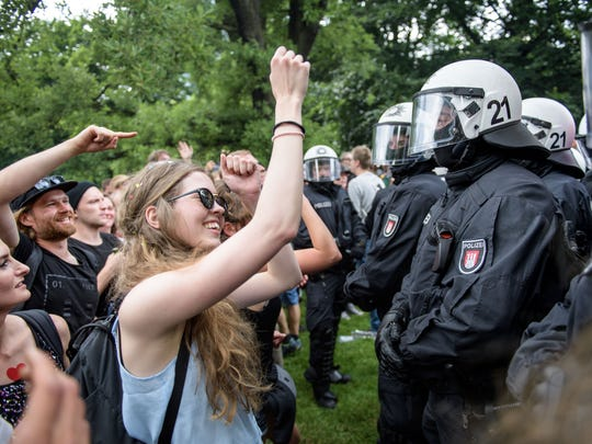 A girl dance to techno music in front of the police