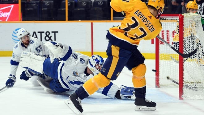 Jan 23, 2018; Nashville, TN, USA; Nashville Predators left wing Viktor Arvidsson (33) scores a goal past Tampa Bay Lightning goalie Louis Domingue (70) during the first period at Bridgestone Arena. Mandatory Credit: Christopher Hanewinckel-USA TODAY Sports