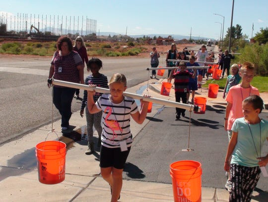 Students carry buckets of water to learn about how