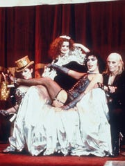 "Actors Tim Curry, center on throne, Patricia Quinn, left, Laura Campbell (Little Nell) and Richard O'Brien, right, appear in a scene from the 1975  film ""The Rocky Horror Picture Show."""