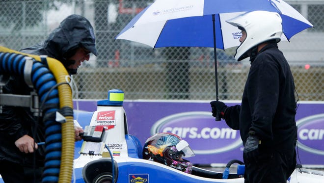 A pit crew member keeps an umbrella over driver Rodolfo Gonzalez in the Dale Coyne Racing car #18 after Gonzalez pull into the pit stop.