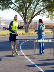 Justin Hill stops for a drink of water at mile 8 at