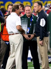 Sandwiched by football friends: MSU head basketball coach Tom Izzo, center, talks with Alabama coach and friend Nick Saban and MSU coach Mark Dantonio before the start of the Cotton Bowl Thursday night in Arlington, Texas.