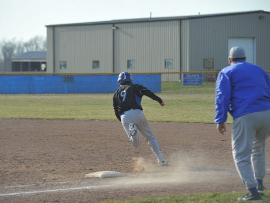 Cody Taylor rounds first base during his RBI triple.