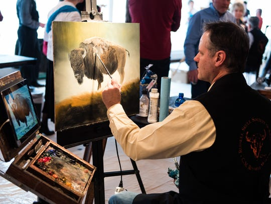 """Joe Kroneberg finishes his piece """"Big Ol' Bull"""" which raised $7,500 for the C.M. Russell Museum Friday during the """"art in Action"""" auction."""