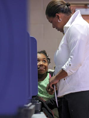 Mylissa Hill, left, 7, looks at her mother Maria Cabrera, right, as she finishes voting at the Anderson Recreation Center precinct on Tuesday.